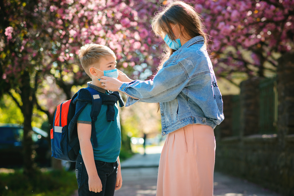 A woman helping her son get ready for school by wearing a surgical face mask