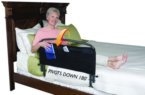 A woman in bed with a bed railing and organizer