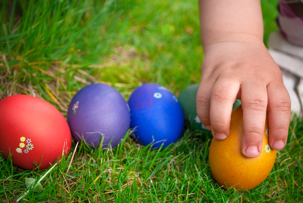 A toddler's hand is picking up one of a cluster of colorful Easter eggs