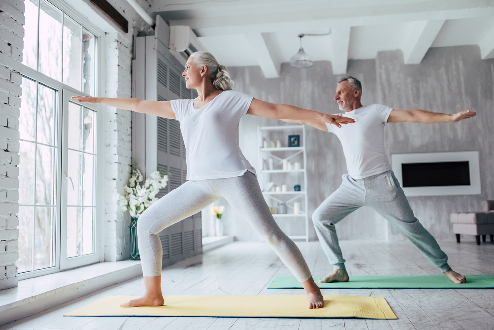 a healthy senior couple doing yoga in their home