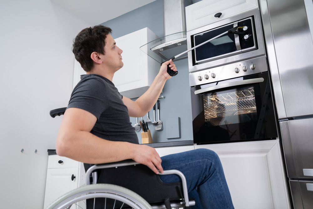 A man in a wheelchair is using a reacher in the kitchen.