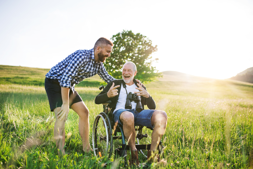 A man with his father in a wheelchair in a field