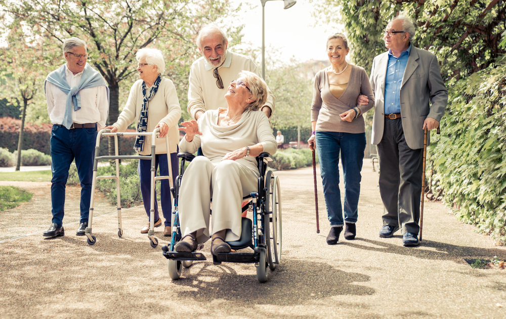 Senior citizens using different mobility devices on a walk.