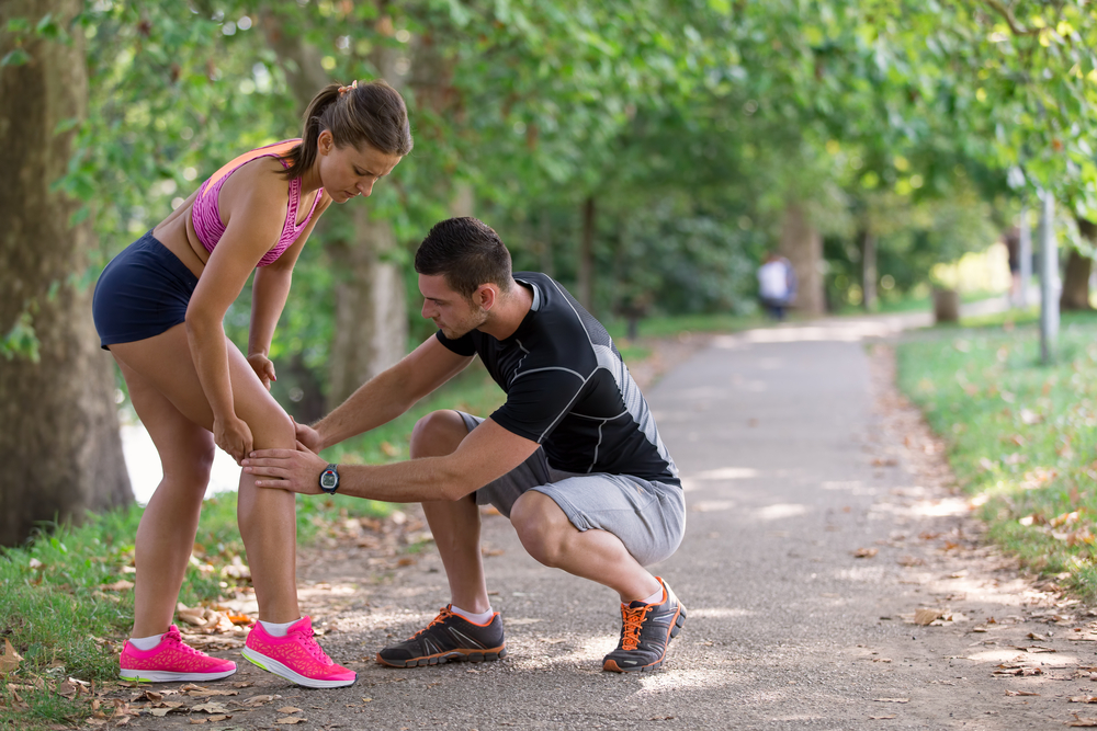 A man is looking a the knee of a woman while the couple is on a run.