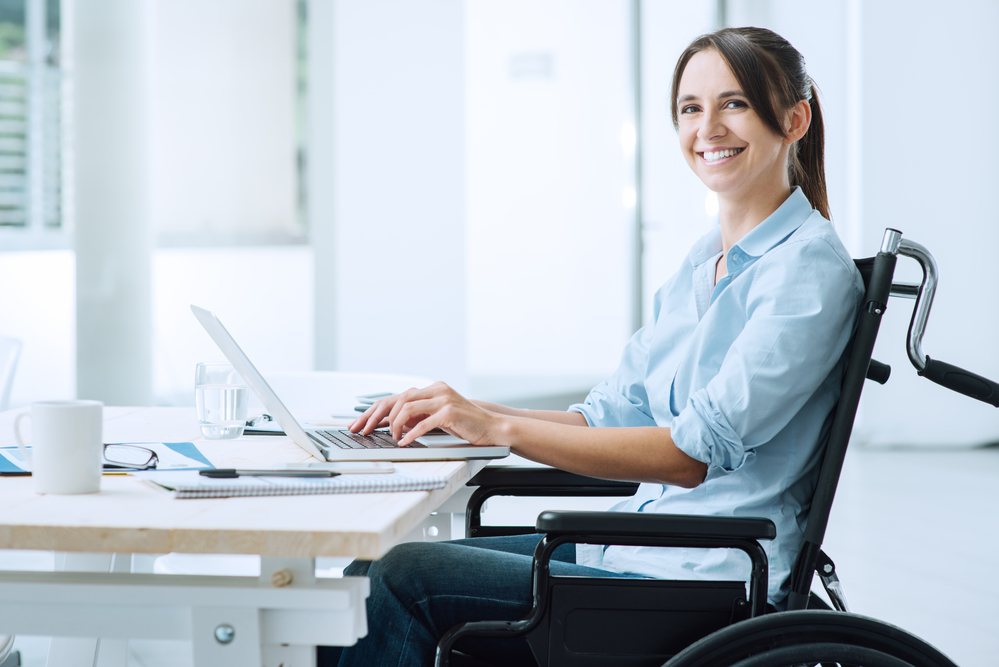 A woman in a wheelchair working at her desk